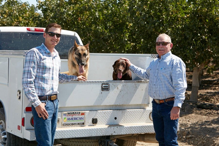 Two Pistachio Growers with a white truck and 2 dogs